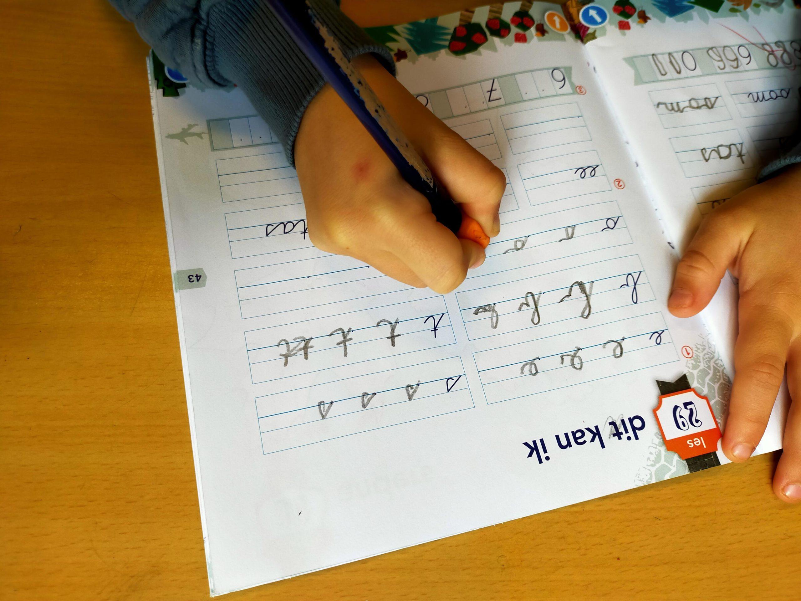 Dit kind uit groep 3 gebruikt een gripper om te leren schrijven